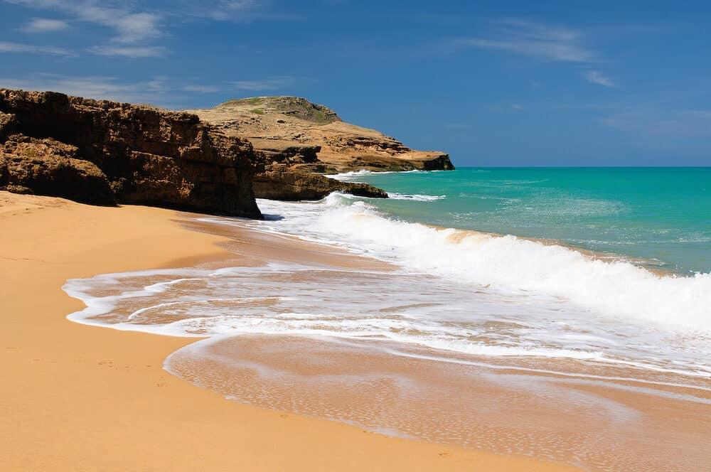 Colombia, wild coastal desert of Penisula la Guajira near the Cabo de la Vela resort. Pilon de Azucar beaches of the Caribbean coast with turquoise water and orange sand