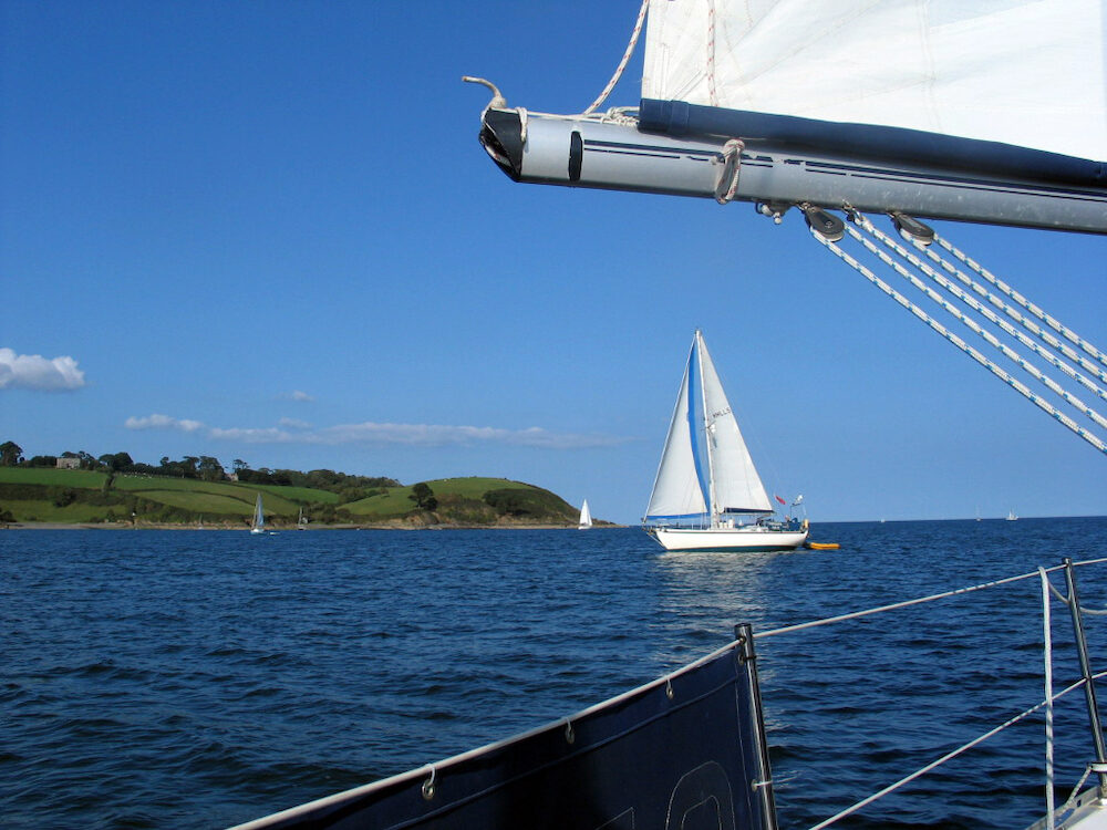 A yacht with white sails against a blue sky framed by a foreground boom and sail. In the background the green slopes of a headland. Cornwall England.