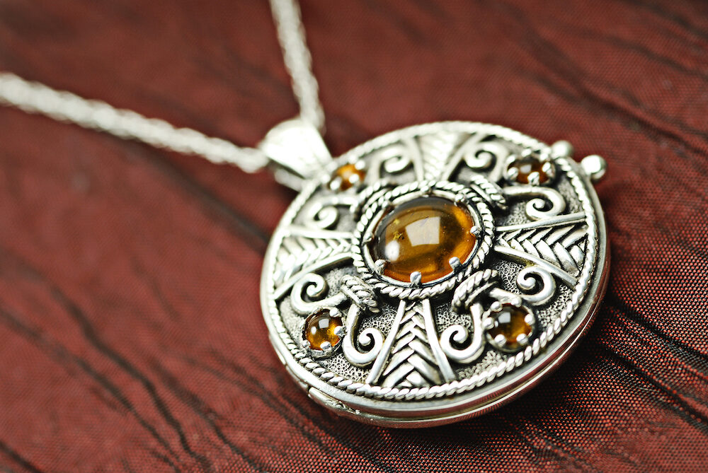 Celtic Siver And Amber Locket on red silk.