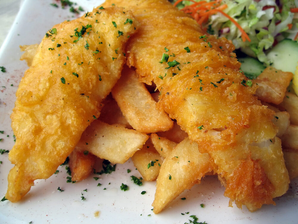 Gourmet fish and chips garnished with parsley flakes and served with side salad.