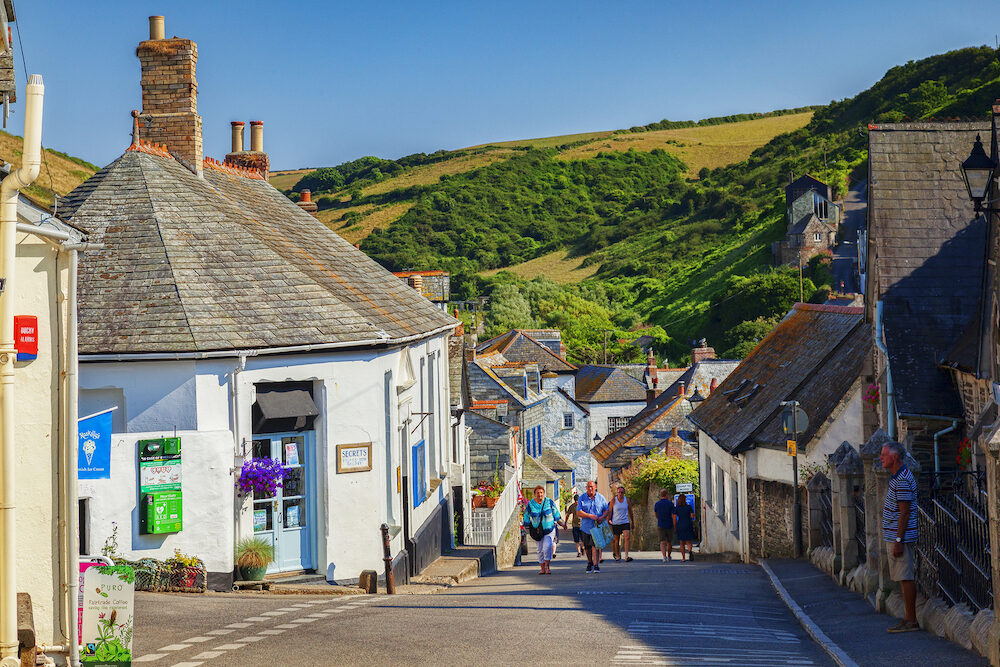 Port Isaac, Cornwall, UK - Group of people walking in Fore Street during the summer heatwave.