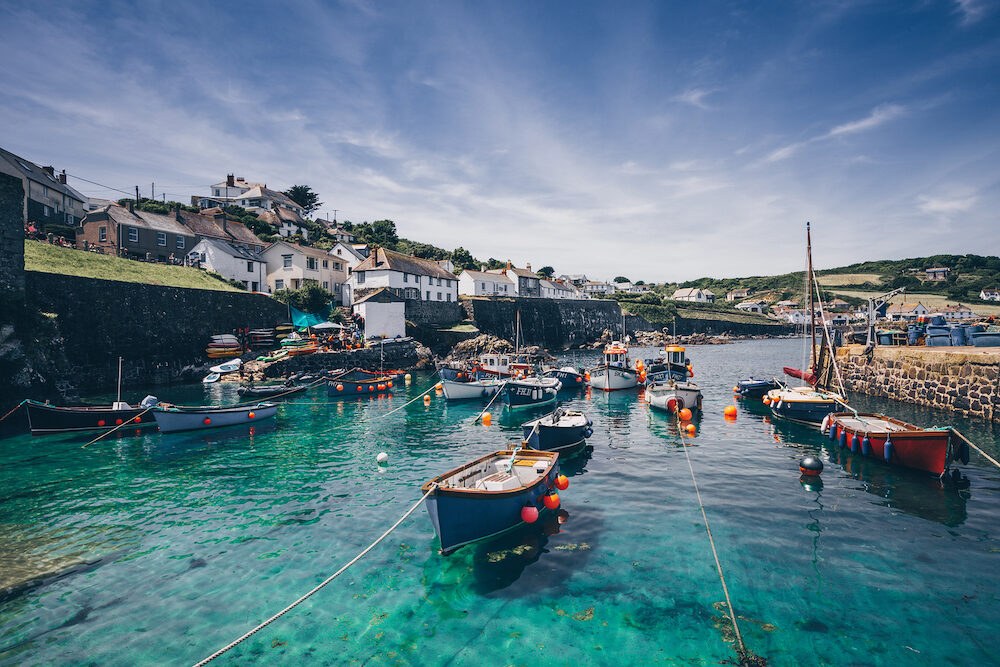 COVERACK, CORNWALL, UK - A landscape image of the picturesque harbour of Coverack in Cornwall, UK with small fishing boats moored in this popular tourist destination