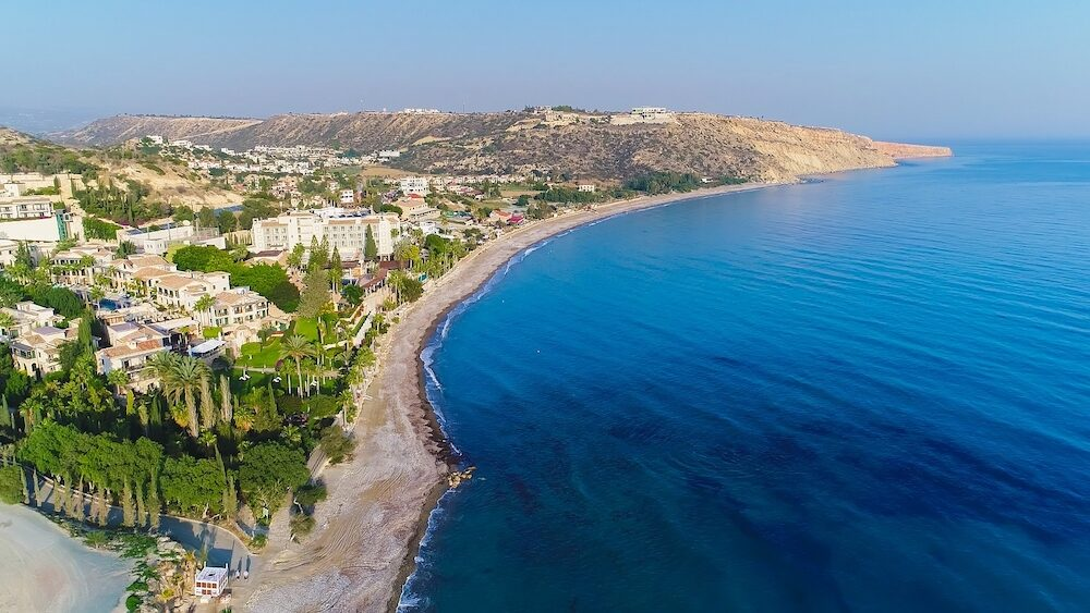 Aerial bird's eye view of Pissouri bay, a village settlement between Limassol and Paphos in Cyprus. Panoramic view of the coast, beach, hotel, resort, hills, plain and building developments from above.
