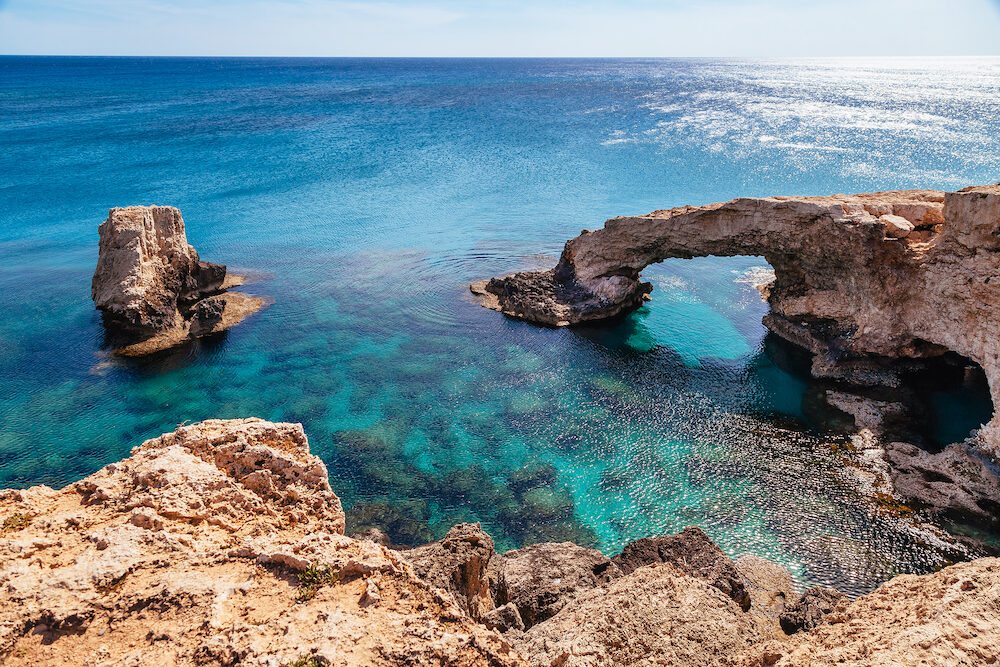 Beautiful natural rock arch near of Ayia Napa Cavo Greco and Protaras on Cyprus island Mediterranean Sea. Legendary bridge lovers. Amazing blue green sea and sunny day.