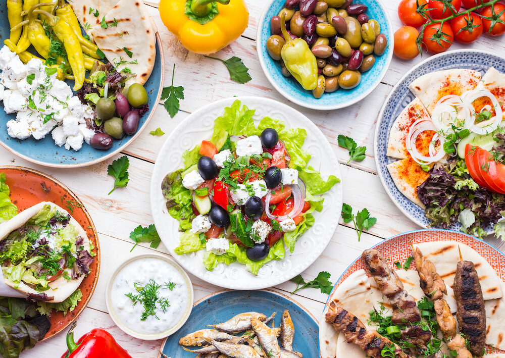 Greek food background. Meze gyros souvlaki fish pita greek salad tzatziki assortment of feta olives and vegetables. Traditional different greek dishes set. Top view. Food for share. Close-up