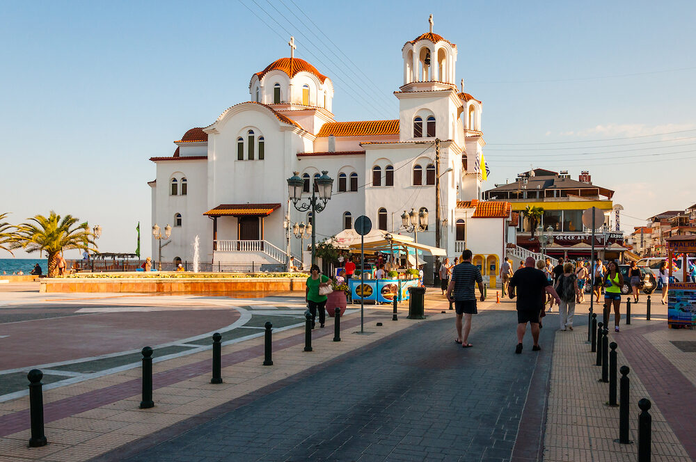 Paralia, Greece - St. Fotini Church or St. Paraskevi Church located on the beach in Paralia resort, Greece. People tourist walking by the street, Aegean sea promenade