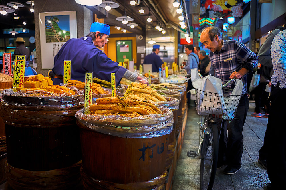 Nishiki Market, Kyoto, Japan - Old man came with his bicycle stood in front of a store which sells variety of pickled food. He was asking for one of them to the vendor.