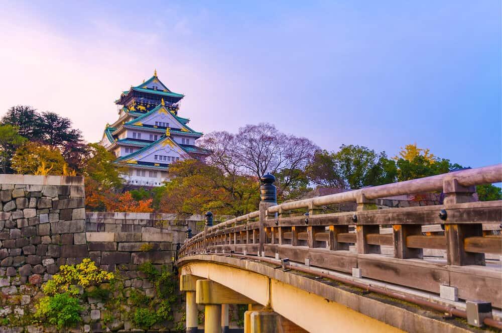 beautiful colorful pastel sunrise of Osaka Castle with autumn leaves, landmark of Osaka, Kansai, Japan