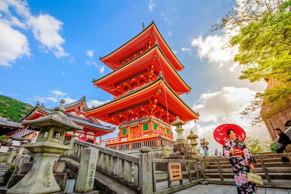 Kyoto, Japan -: woman wear kimono and parasol standing in red Pagoda of Kiyomizu Temple. Kiyomizudera is Unesco Heritage and popular landmark in Kyoto. Spring season, sunset shot