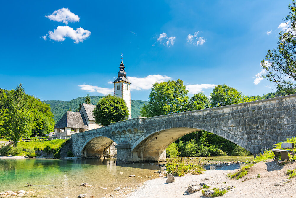 Bohinj bridge and church, Slovenia. Look to old historic ancient bridge and the church near the Bohinj lake, in Triglav national park. The Ribcev Laz village. Sunny sky with clouds, summer weather.