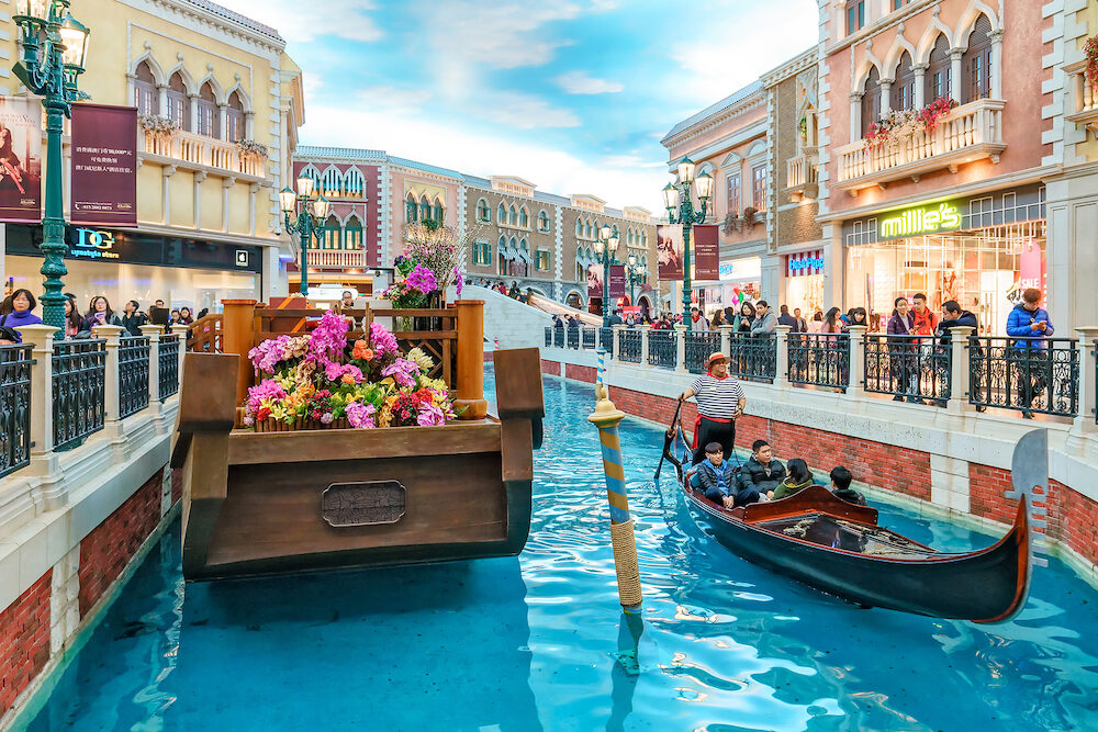 Macau - Gondolier rides tourists in gondola along mock canal of Venetian Macau hotel and casino.