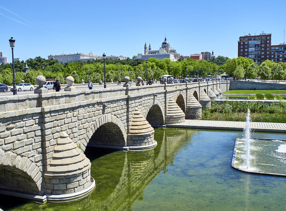 Madrid, Spain - . Puente de Segovia bridge crossing the gardens of Madrid Rio at spring day with the Almudena Cathedral and the Royal Palace in background. Madrid, Spain.