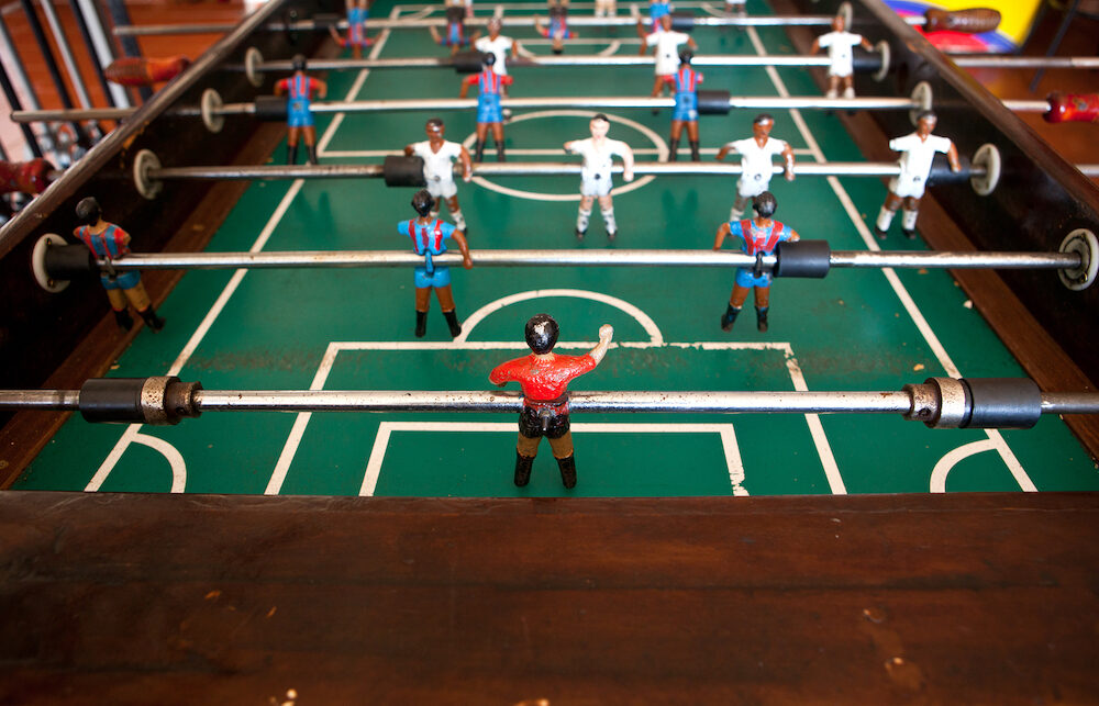 Table football in the bar visible figures of toy mini football players wearing Real Madrid and Barcelona soccer team