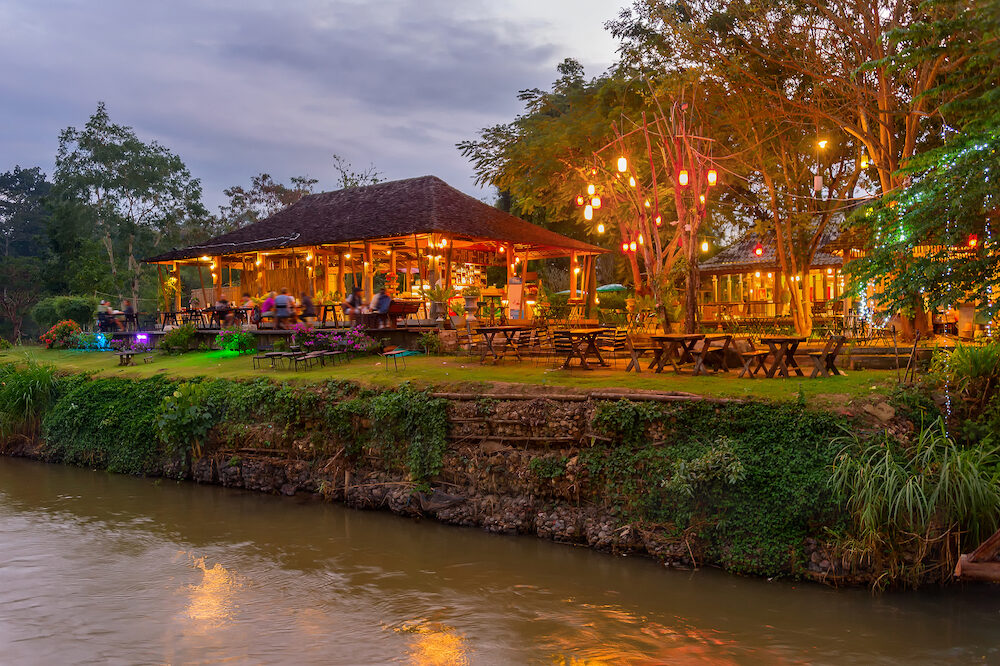 Evening scene with illuminated outdoor restaurant by the river in tropical jungle, Pai, Thailand