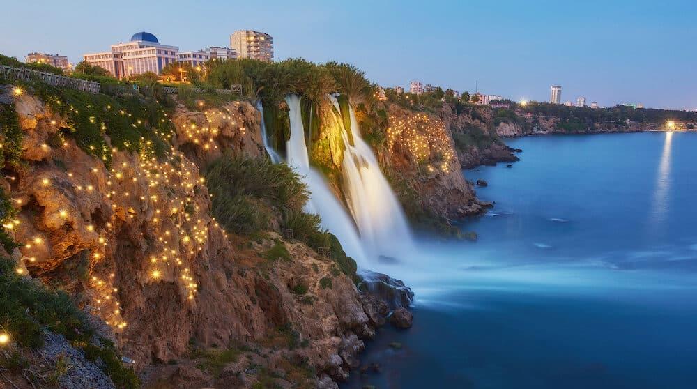 Night view of water cascading from platform into Mediterranean sea in Antalya. Illuninated Lower Duden Waterfall in popular seaside resort city Antalya, Turkey.