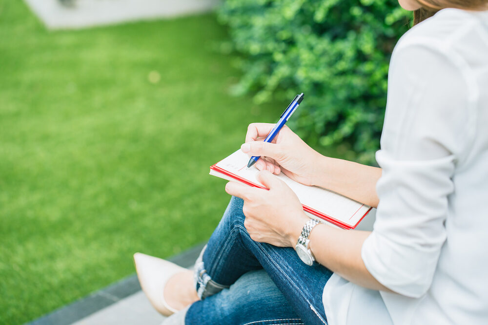student writing at park working outdoor women work business job writer write text in notebook.