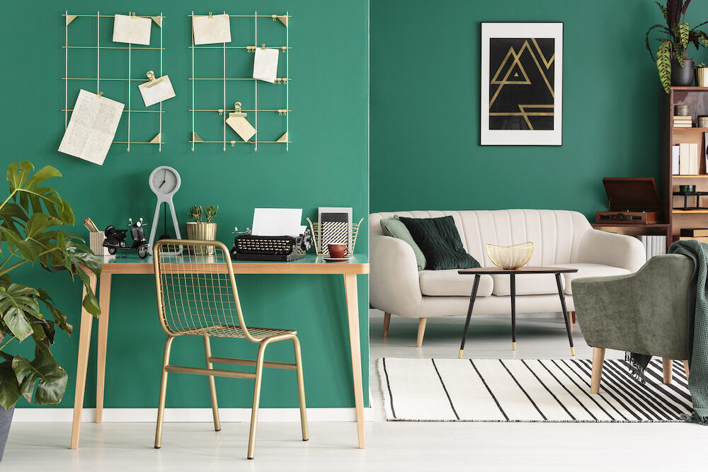 A freelance writer's home office with a typewriter by a green wall with golden frame organizer in a hipster living room interior