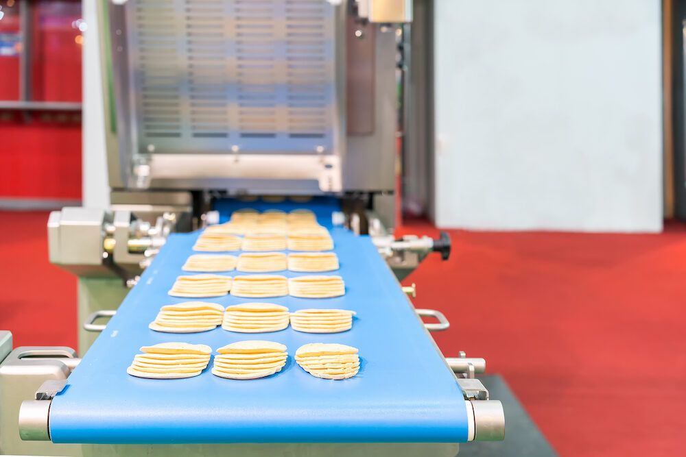 Close up bologna sliced plate on conveyor of automatic slicer machine for industrial food manufacture