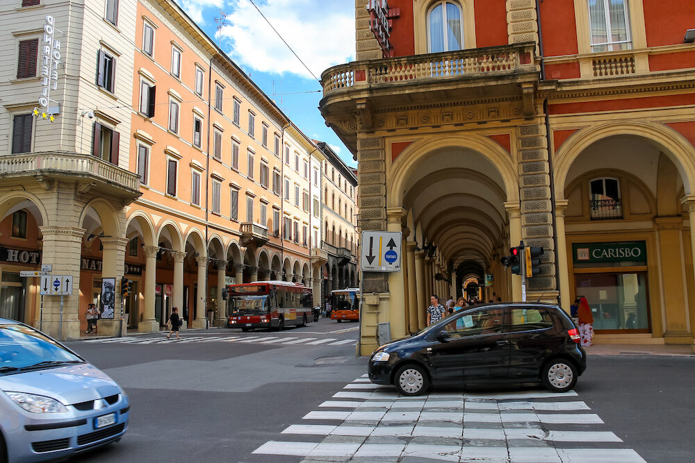 Bologna Italy - People and vehicles at the intersection of Via dell'Indipendenza and Via Irnerio in Bologna Italy