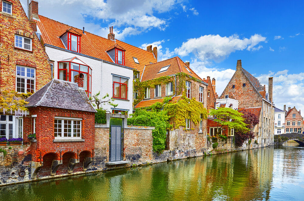 Bruges, Belgium. Medieval vintage brick houses with balconies over river with old bridge, covered with green plants and bushes. Summer landscape with blue sky and clouds.