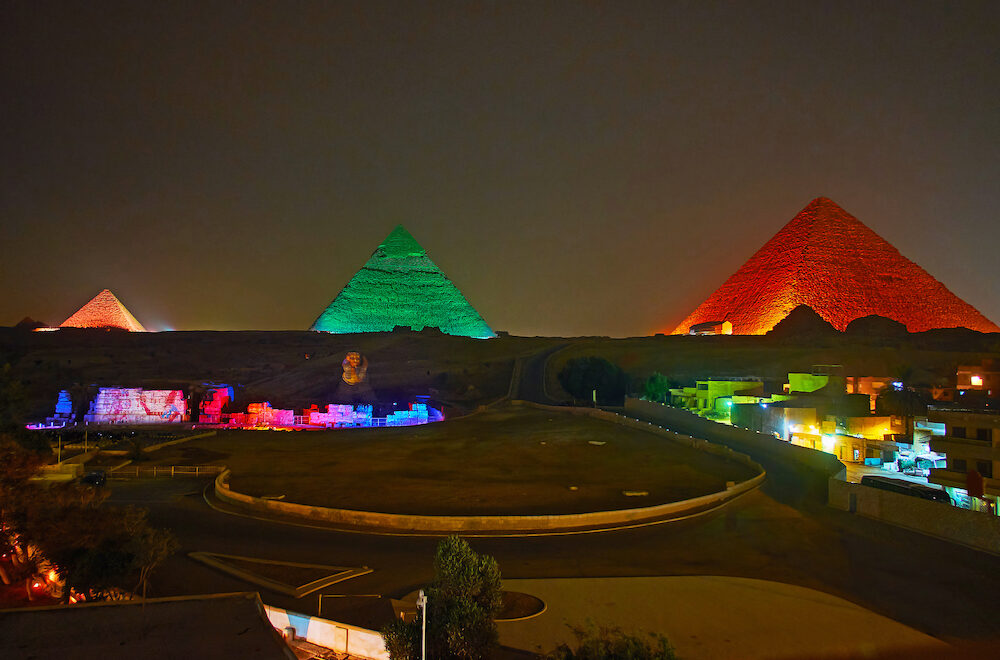 The light show in Giza Necropolis - bright lights on ancient Pyramids and Great Sphinx make this place one of the most interesting for evening visit, Cairo, Egypt.