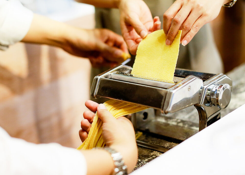 Chef making pasta with a machine, home made fresh pasta