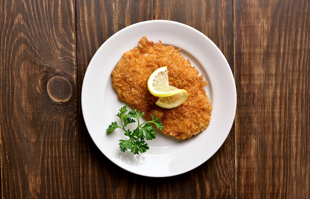 Chicken schnitzel on plate over wooden background with copy space. Top view, flat lay