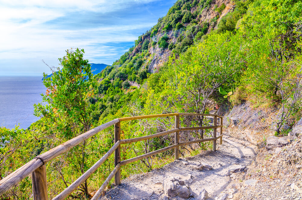 Pedestrian hiking stone path trail with railing between Corniglia and Vernazza villages with green trees, blue sky background, National park Cinque Terre, La Spezia province, Liguria, Italy