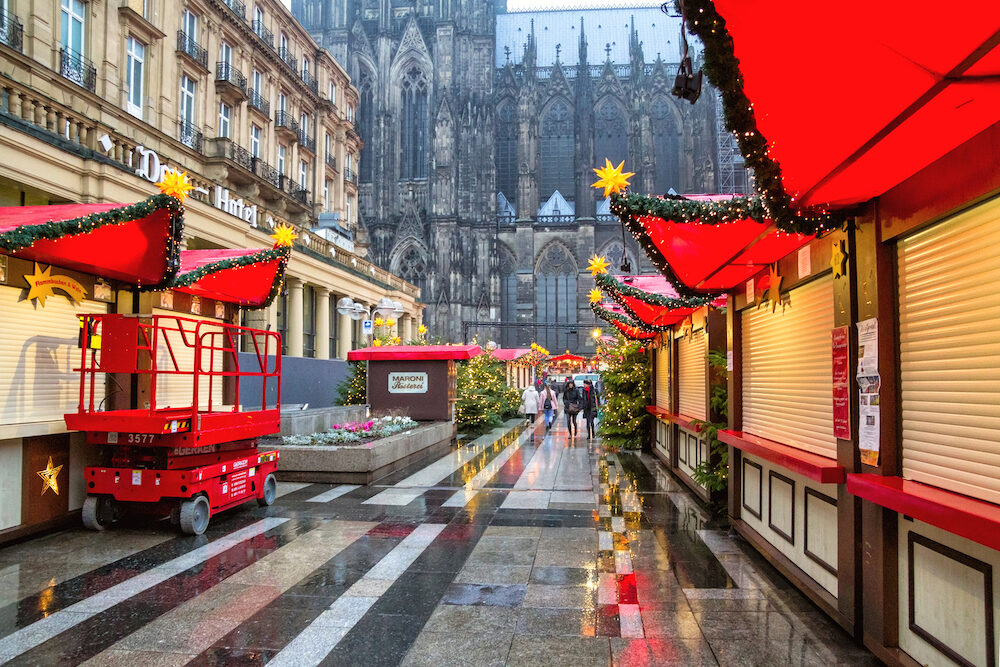 Holiday cityscape - view of the Christmas Market (Weihnachtsmarkt) early morning on background the Cologne Cathedral, Germany