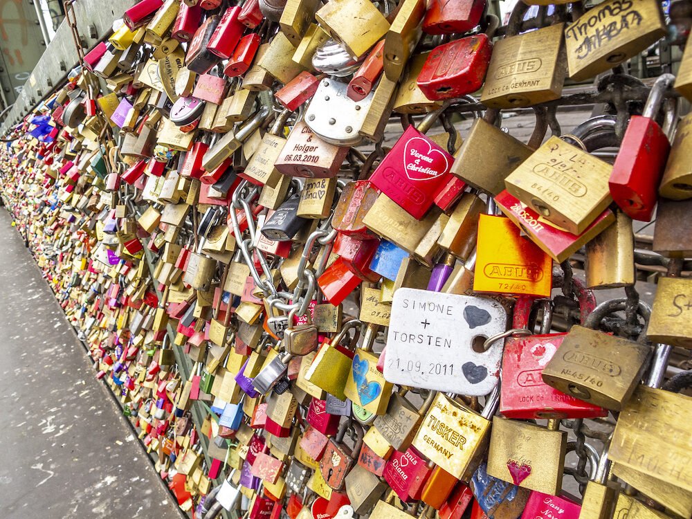 COLOGNE, GERMANY - Numerous love padlocks on the fence between the footpath and the railway lines of Hohenzollern Bridge