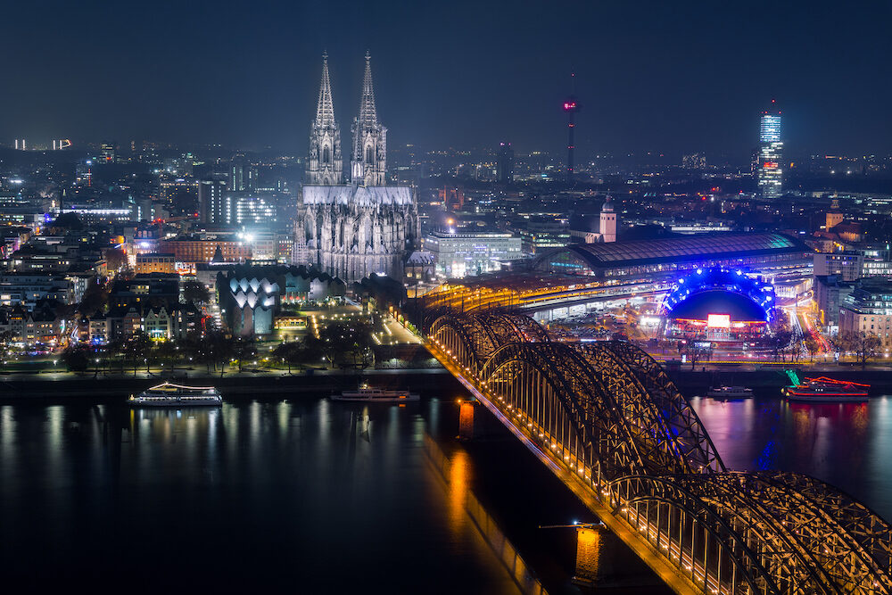 View of the illuminated City of Cologne, the Cologne Cathedral, the Hohenzollernbridge and the River Rhine at Night - in Germany Cologne