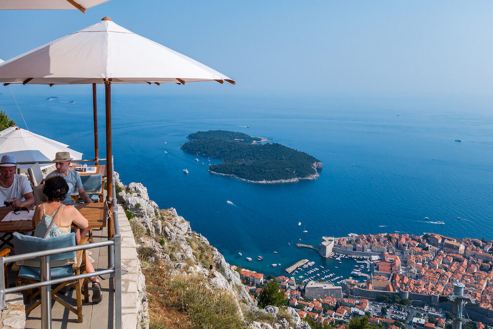People in a restaurant above Dubrovnik. Dubrovnik, Croatia - Two men and one woman in a restaurant on top of the mountain above Dubrovnik. Summer view of Dubrovnik.