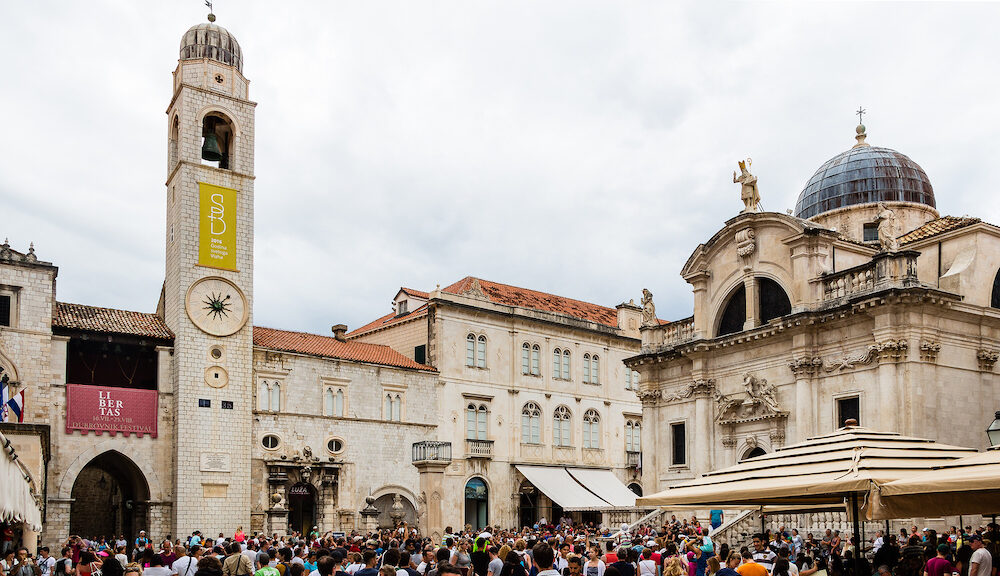 DUBROVNIK CROATIA - Stradun street (Placa) ending square in Old Town with the neoclassical architecture of Saint Blaise church Orlando's Column and Clock Tower beside Sponza Palace.