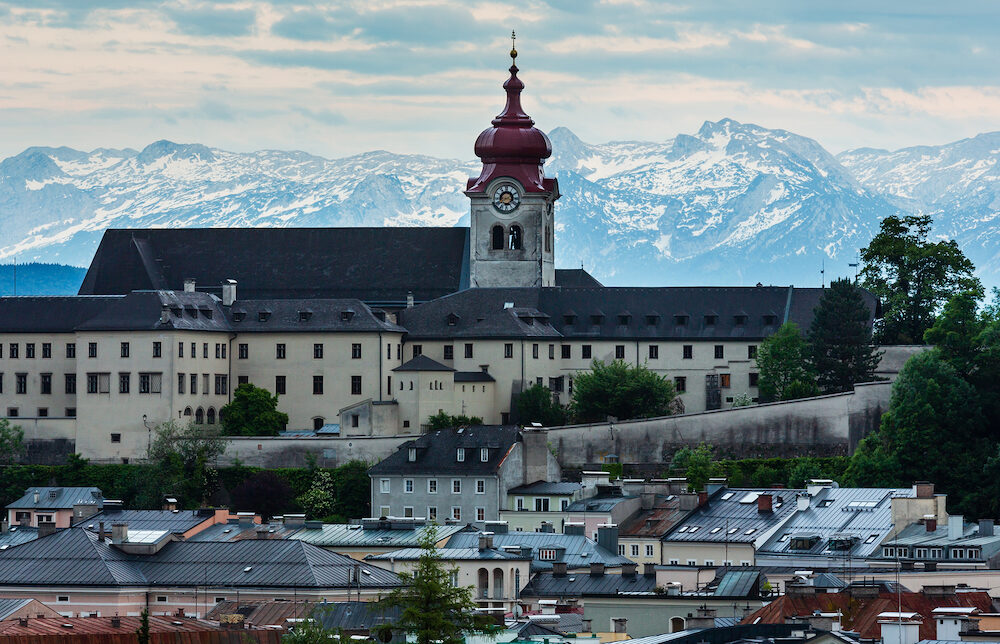 Evening summer Salzburg City (Austria) view from up with Nonnberg Abbey Benedictine monastery (refurbishment in the Baroque style in the 1880s) abd Alps mountain in far.