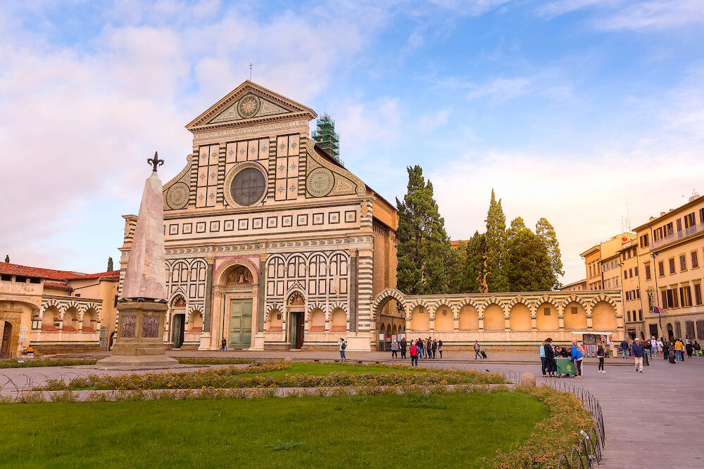 Florence, Italy - Facade of the Basilica of Santa Maria Novella on blue sky background and people