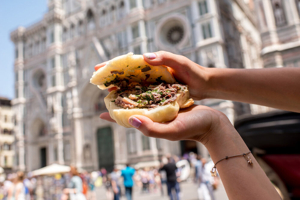 Holding lampredotto sandwich on the Duomo background in Florence. Lampredotto is a typical Florentine dish made from the stomach of a cow