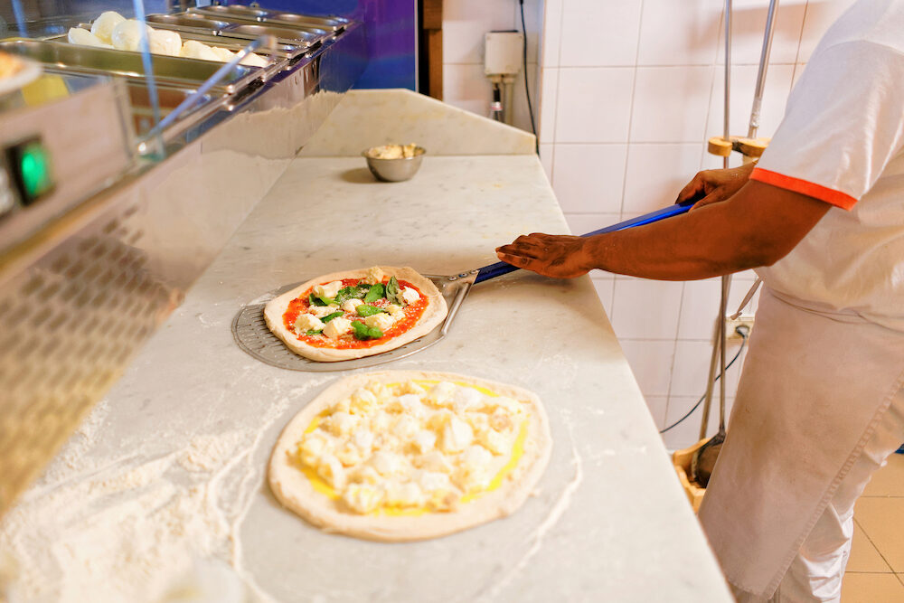 Preparation of homemade pizza in pizzeria restaurant Florence Tuscany Italy.