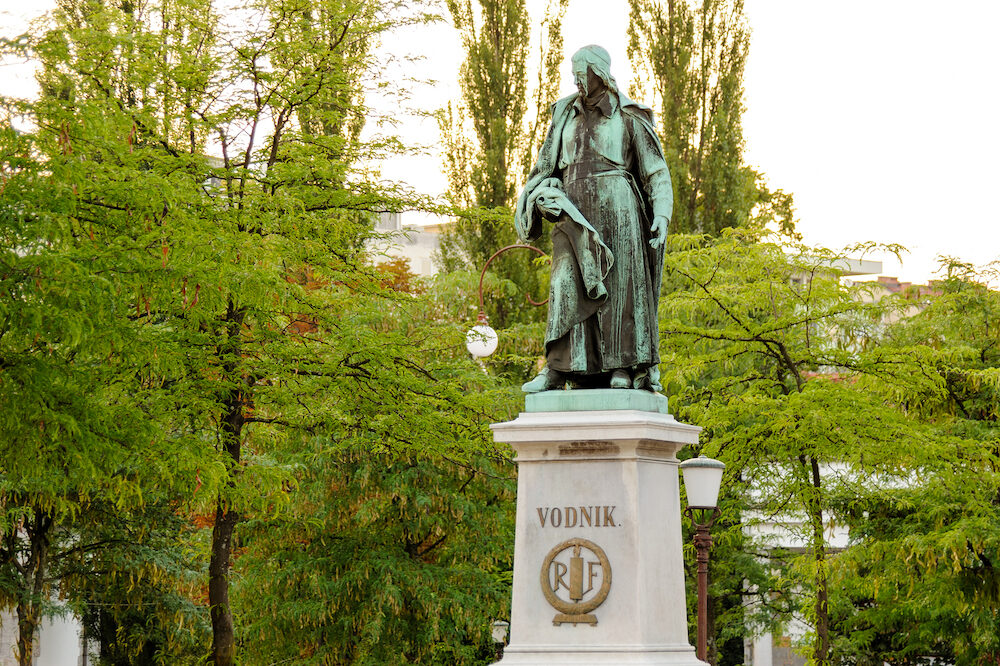 LJUBLJANA SLOVENIA - : Statue of Valentin Vodnik on a stone pedestal a Slovene priest journalist and poet at Vodnik square near the Central Market. RF stands for Republique Francaise