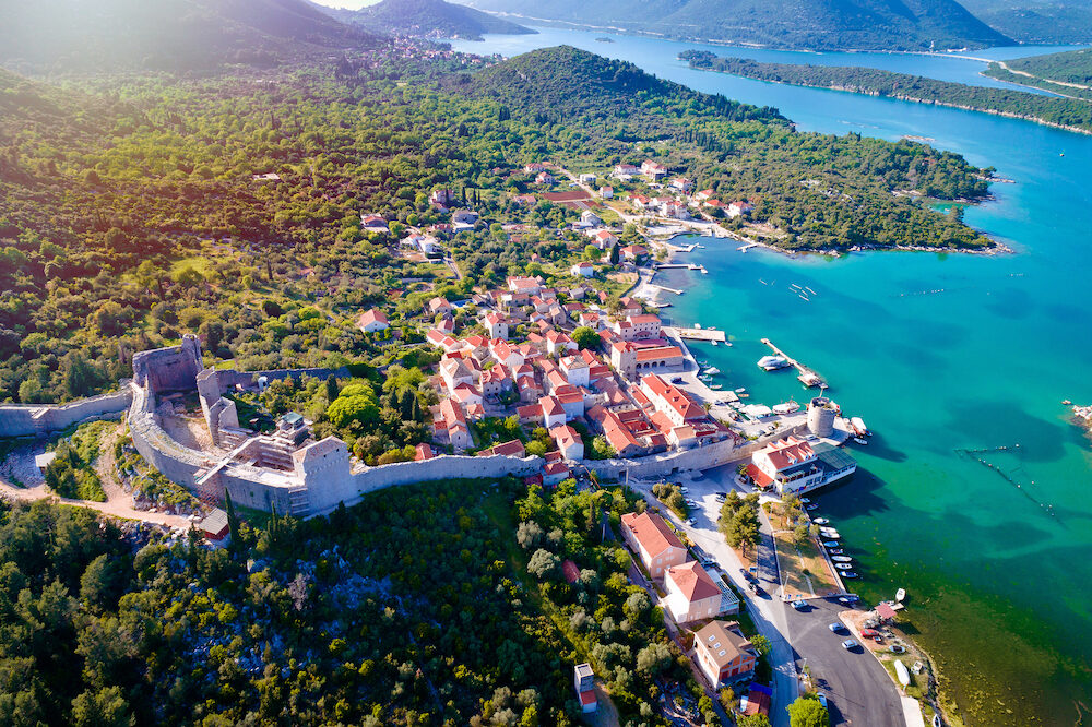 Mali Ston waterfront aerial sun haze view, Ston walls in Dalmatia region of Croatia