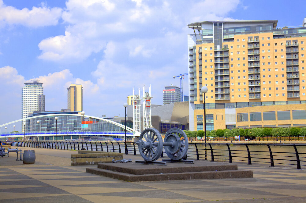 Promenade view with Millennium Bridge and modern buildings at Salford Quays in Manchester.
