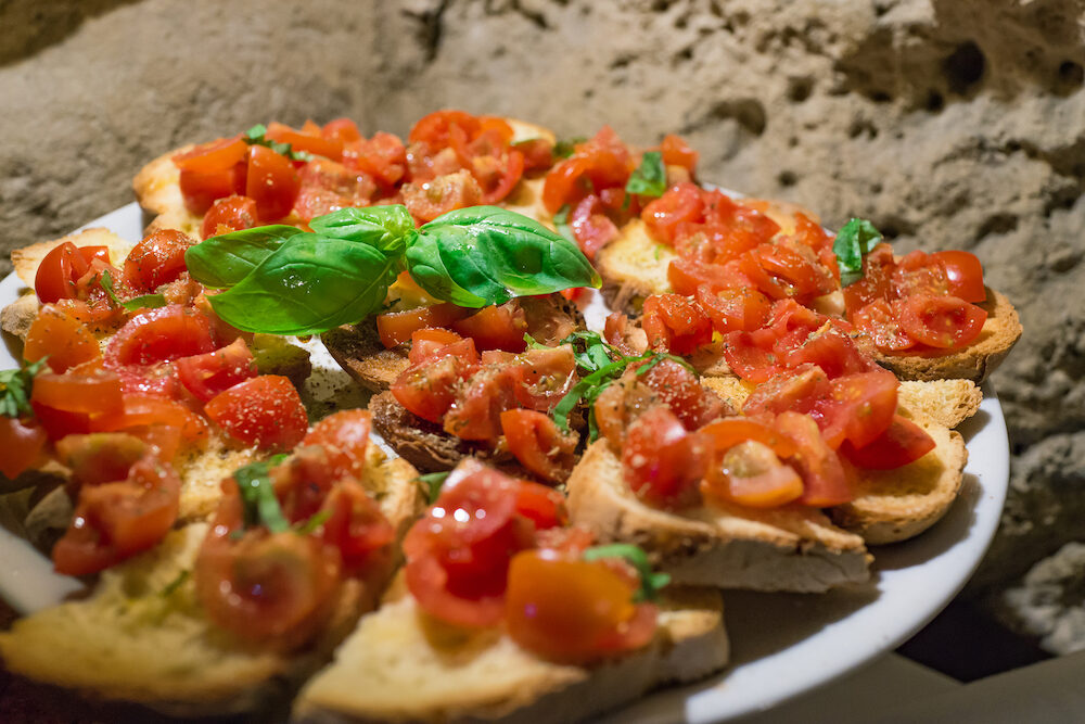 Closed up of Italian bruschettas with chopped tomato and basil ready for breakfast