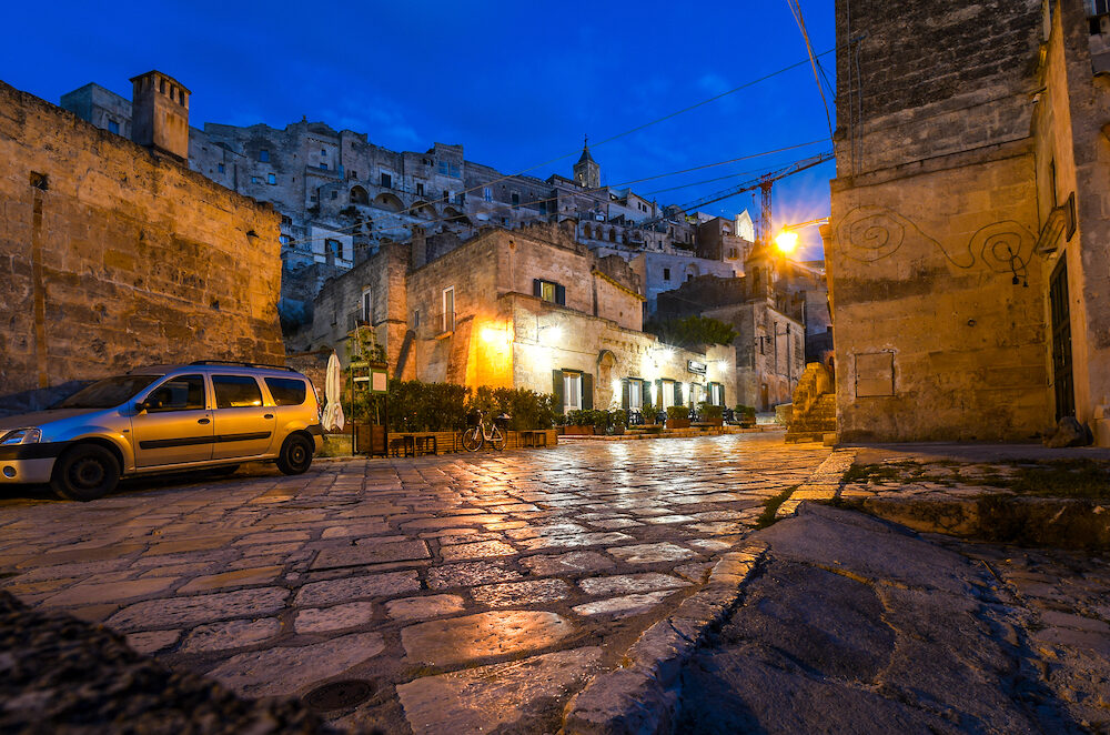 Matera, Italy - Night view, street level of an illuminated cafe in the historic, medieval center of the ancient city of Matera Italy.