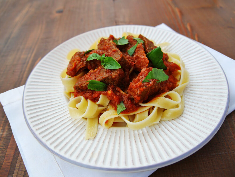 Neapolitan ragu with tagliatelle pasta on plate over wooden table.