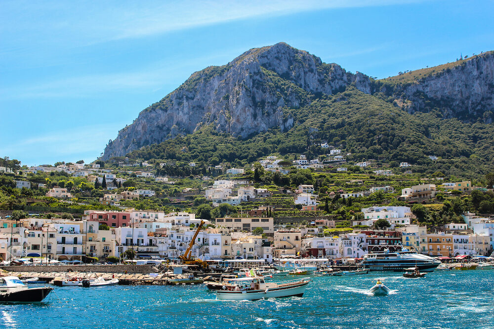 Capri, Italy- Busy beach with boats docked and people walking in the island of Capri , Italy