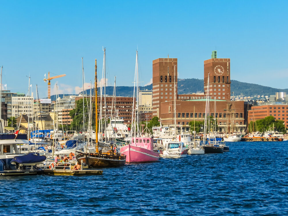 OSLO, NORWAY - Oslo Harbour and Radhuset building, Oslo City Hall. Promenade along the seafront Old Port Oslo. View of the shore of Oslofjord, Norway