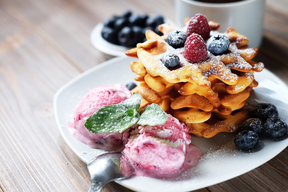Plate of belgian waffles with ice cream and fresh berries - raspberries and blueberries