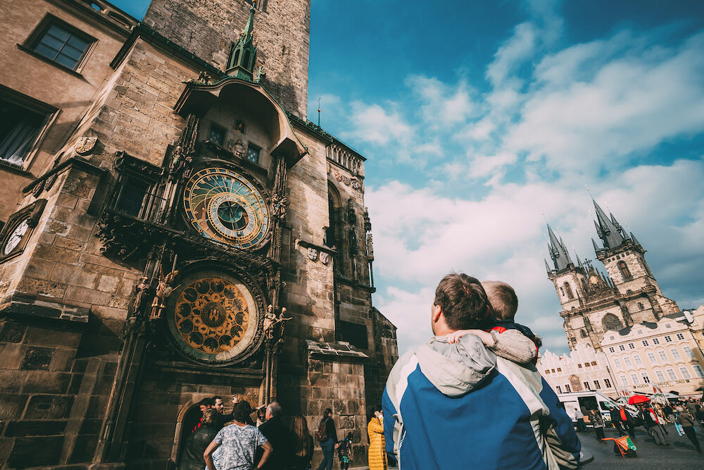 PRAGUE, CZECH REPUBLIC - The unrecognizable man and boy are looking at astronomical clock in Prague. Tower of town hall with astronomical clock, or Prague orloj in Prague, Czech Republic.