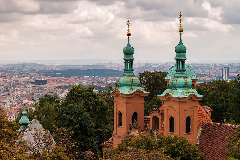 Towers of Cathedral of Saint Lawrence (Prague) with the city of Prague in the background, on an overcast autumn day. Cityscape in Europe.