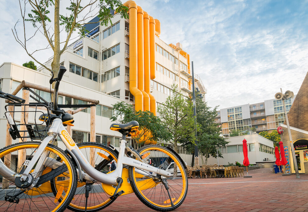 ROTTERDAM HOLLAND- ; Two yellow and white share bikes leaning against tree in front of city library building with bright yellow external air-conditioning ducts in city square