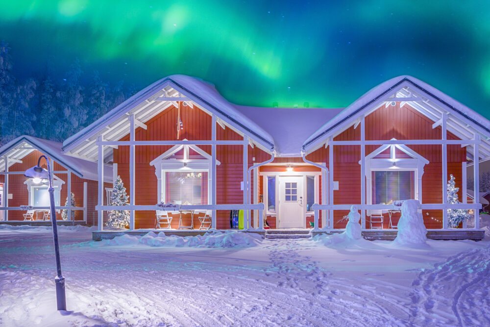 Travel Destinations Concepts. Beautiful Multicoloured Vibrant Aurora Borealis known as Northern Lights Playing with Vivid Colors Over Traditional Lapland Houses in Finland.Horizontal Orientation